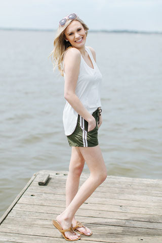 Blonde woman smiling on a lake dock wearing tank top and olive track shorts