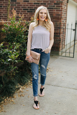Blonde woman walking in sun in cute outfit with jeans and striped top