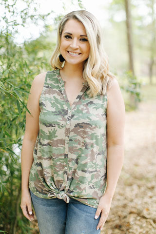 Blonde woman outdoors wearing cute camo sleeveless blouse and light denim jeans