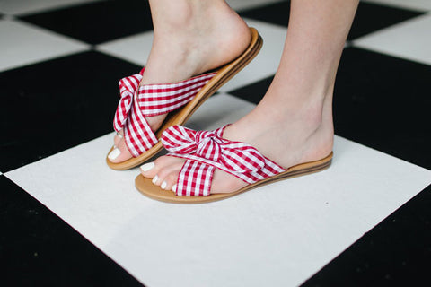 Woman's feet wearing sandals with fabric red-and-white checker print
