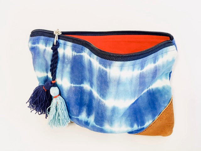 This blue and white cotton and leather pouch features the shibori tie-dye techniques famous in Rajasthani textile craft. Made by women artisans, according to fair trade principles, this beautiful and versatile piece is useful as a stash for your art supplies, cosmetics, or even as an evening clutch.