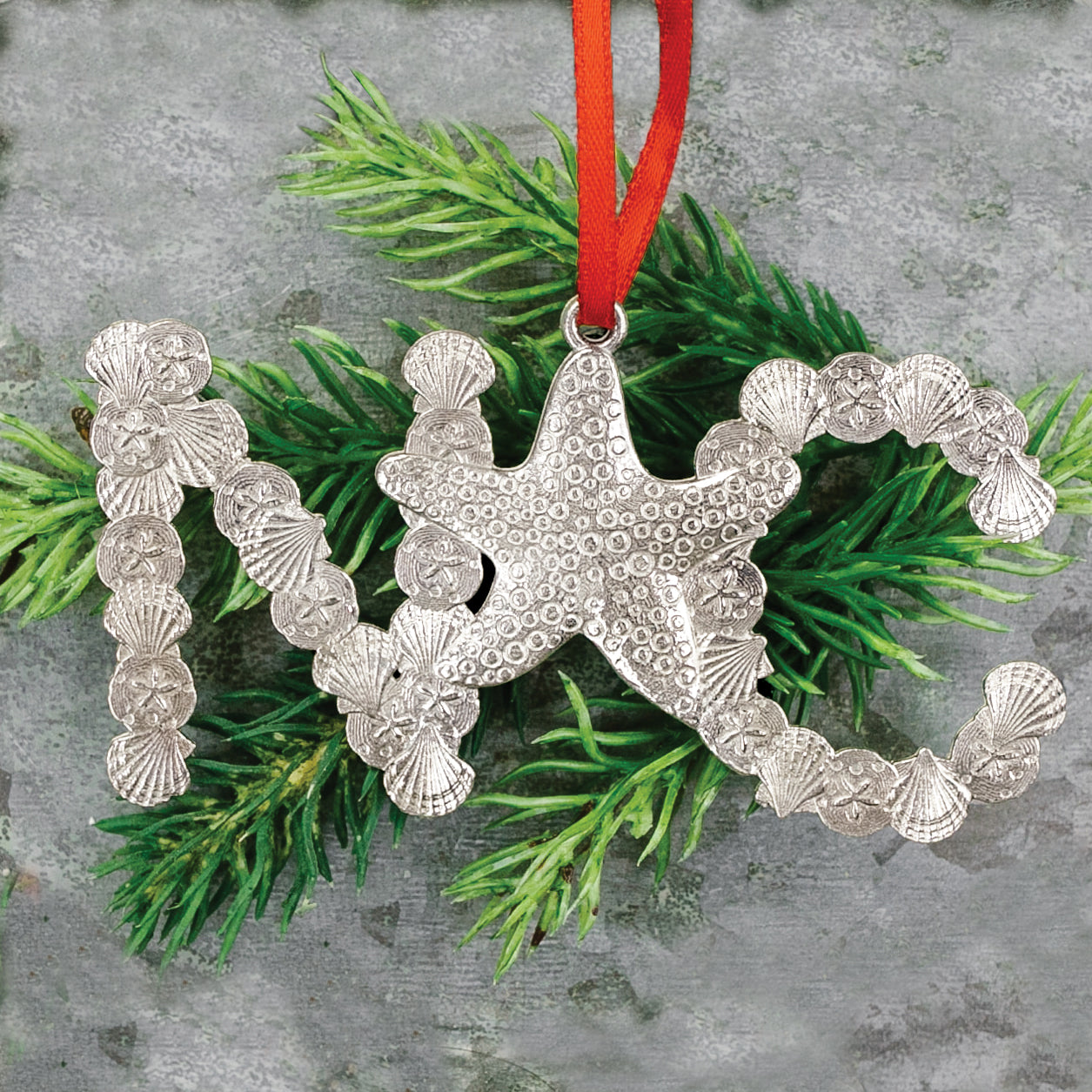 A pewter holiday Christmas tree ornament that says NC with starfish and seashells on a fir branch.