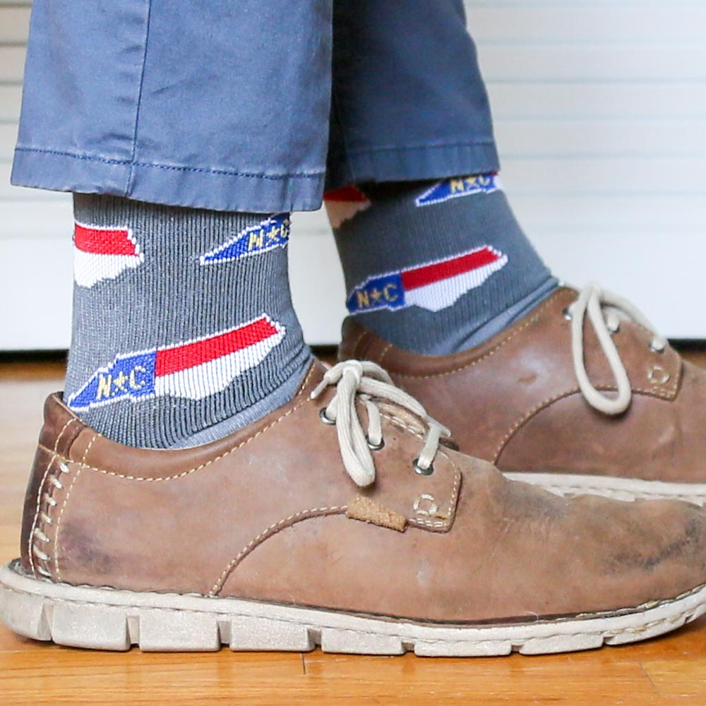 A man wearing a pair of gray socks with the state shape of North Carolina in the red, white, and blue flag colors.