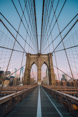 Centered exactly on the Brooklyn Bridge, the massive steel and granite structure stands tall with the New York skyline in the background.