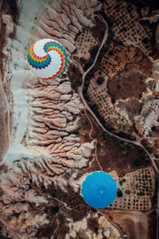 The viewpoint looks directly down onto two hot air ballons taking off from the brown and green terrain below.