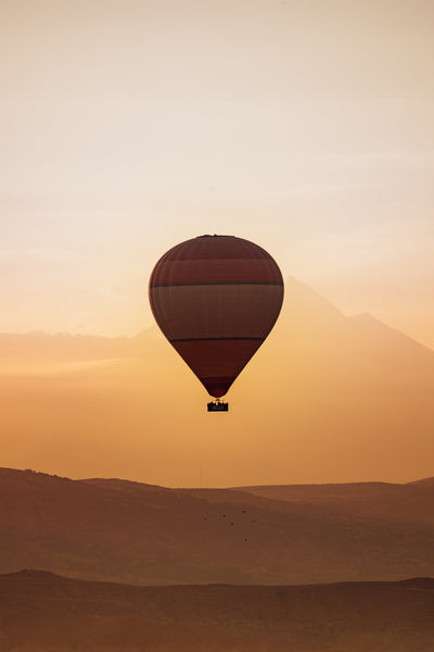 A single hot air balloon floating through the sunrise soaked sky with faint mountainous landscapes in the background