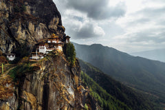 The Tiger's Nest Monastery sits along the mountainside as sun shines through the clouds.