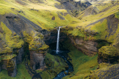 A lush, green landscape with a waterfall in the center draining into a small river.