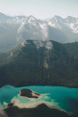 Shot from the sky, a small forested island sit inside a vast blue-green lake in the valley of snow-capped mountains.