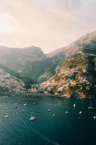 A cliffside town peers over the sea as boats sail in and out.