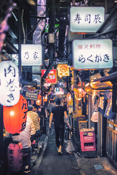 A lone photographer walks down an alley filled with colorful signs written in Japanese.
