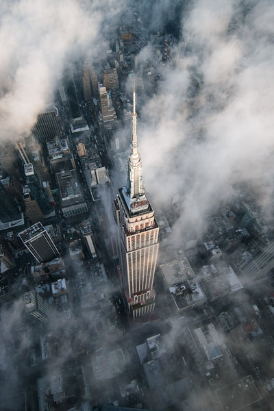 Taken from above the Empire State Building, the view peers down onto the top from an angle and showcases the steel city below as clouds sporatically cover it.