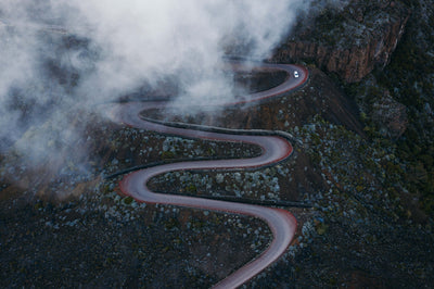 Taken from above, an S-shaped curvy road moves down the mountainside with lush greenery surrounding it and clouds covering.