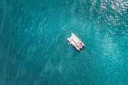An aerial shot showing a single white, gleaming catamaran surrounded by a turquoise, clear ocean.