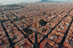 An aerial shot depicting the geometrical blocks of a city scape with red roofs and the large, detailed La Sagrada Familia in the center.