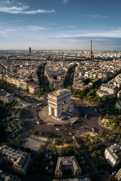 The Arc de Triomphe surrounded a traffic circle with exits points in various ways detailing the geometry of Paris, with the Eiffel Tower in the background.