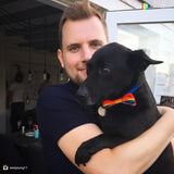 A man holds a small black dog who wears a Pride Rainbow knitted Bow Tow