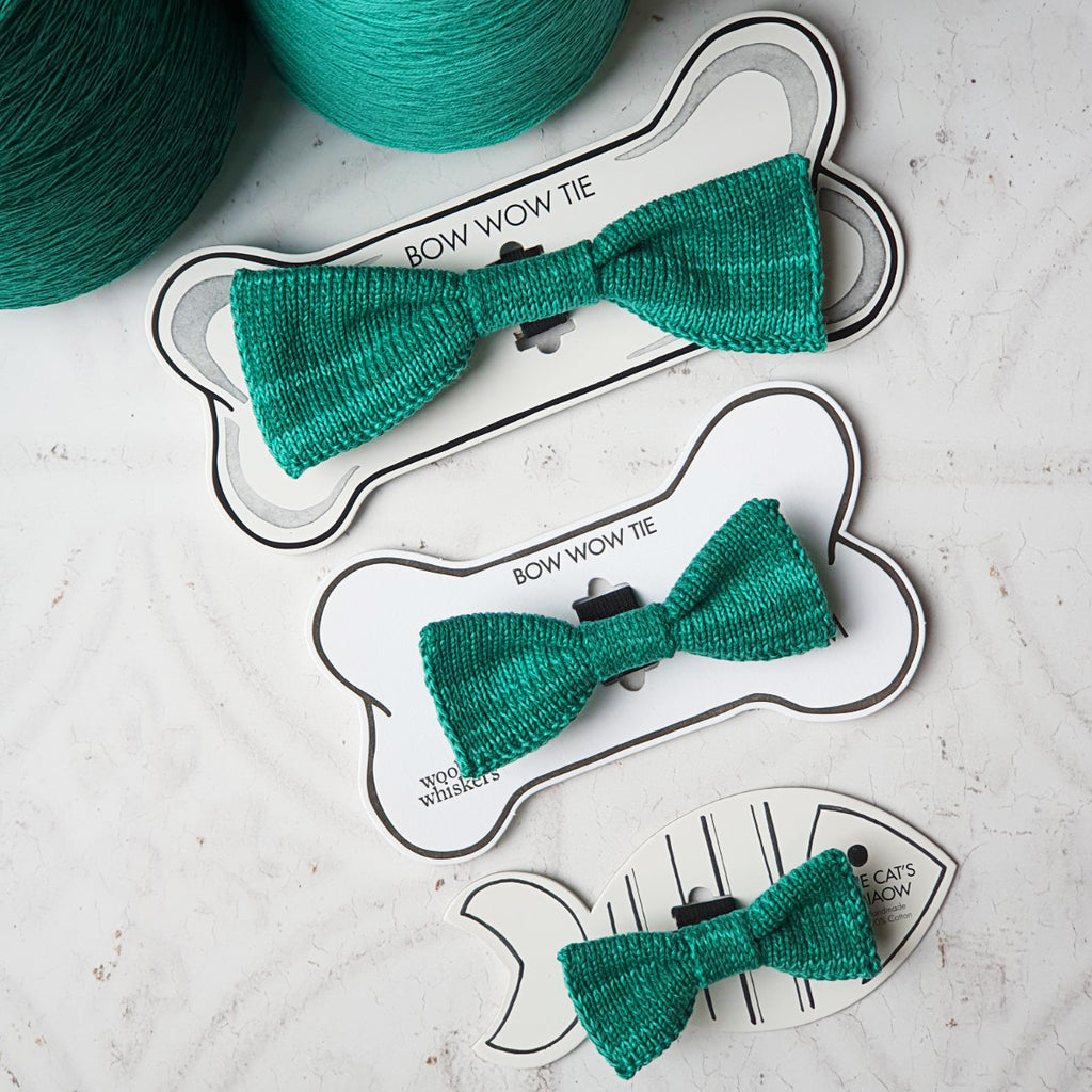 Green Knitted Cat and Dog Bow Ties laid flat beside cones of yarn