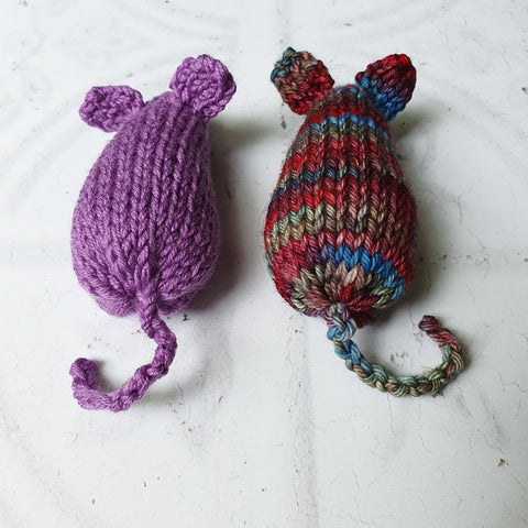 Rear view of two knitted mice cat toys with tails