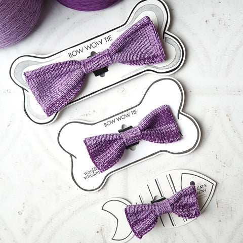 Purple Cat and Dog Bow Ties ladi flat beside cones of yarn