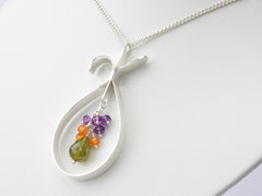 Chloris necklace. Handmade polished sterling silver 'teardrop' shape with amethysts, carnelians and a vesuvianite drop suspended within it . Harmony Collection. 45cm chain. 5.1cm long pendant