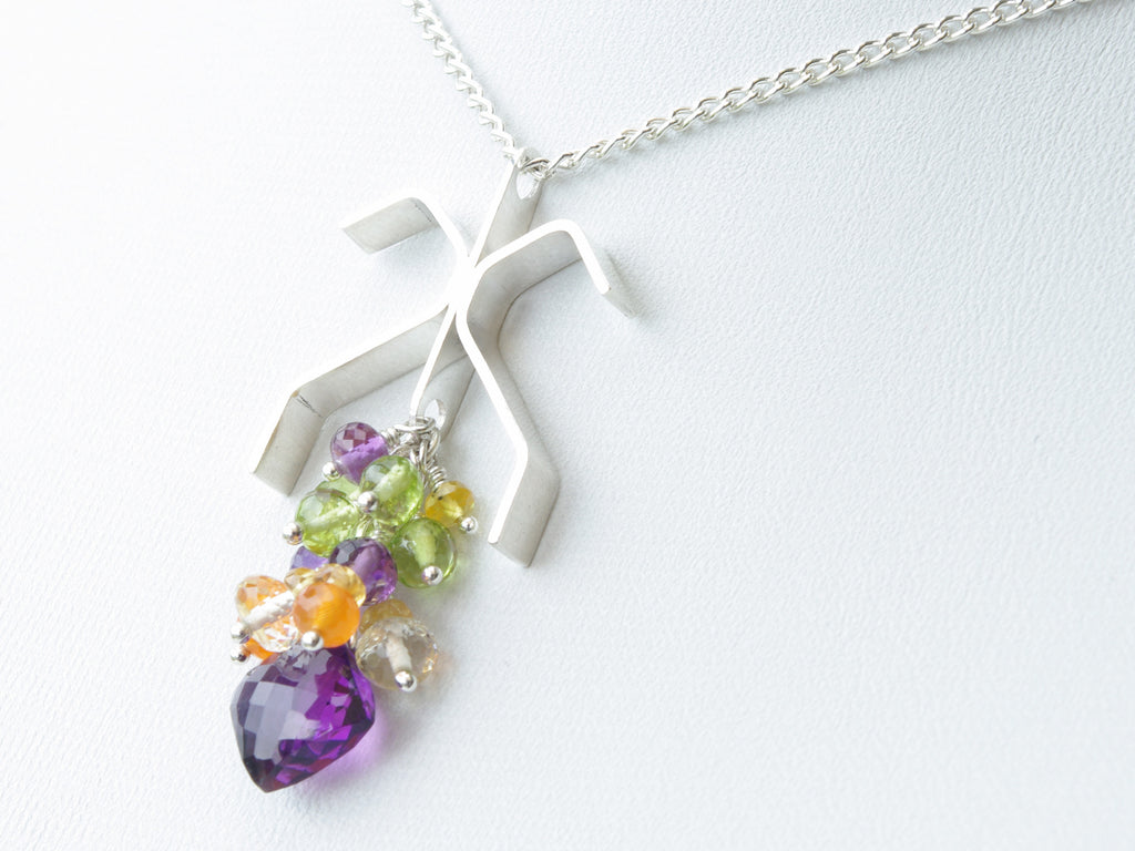 Copia necklace. Handmade polished sterling silver 'diamond' shape with amethysts, yellow sapphire, peridot, carnelian and scapolite suspended within it . Harmony Collection. 46cm chain. 4.1cm long pendant