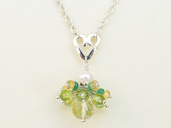 Persephone necklace. Emeralds, yellow sapphires and peridots with a white freshwater cultured pearl and citrine. Suspended from a polished sterling silver handmade heart on a sterling silver chain. Unique. 46cm chain. 3cm pendant