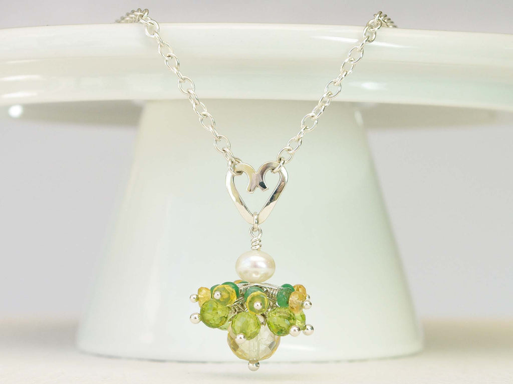 Persephone necklace. Emeralds, yellow sapphires and peridots with a white freshwater cultured pearl and citrine. Suspended from a polished sterling silver handmade heart on a sterling silver chain. Sweet Heart Collection. 46cm chain. 3cm pendant