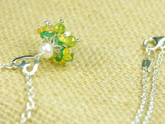 Persephone necklace. Emeralds, yellow sapphires and peridots with a white freshwater cultured pearl and citrine. Suspended from a polished sterling silver handmade heart on a sterling silver chain. Sterling silver necklace. 46cm chain. 3cm pendant