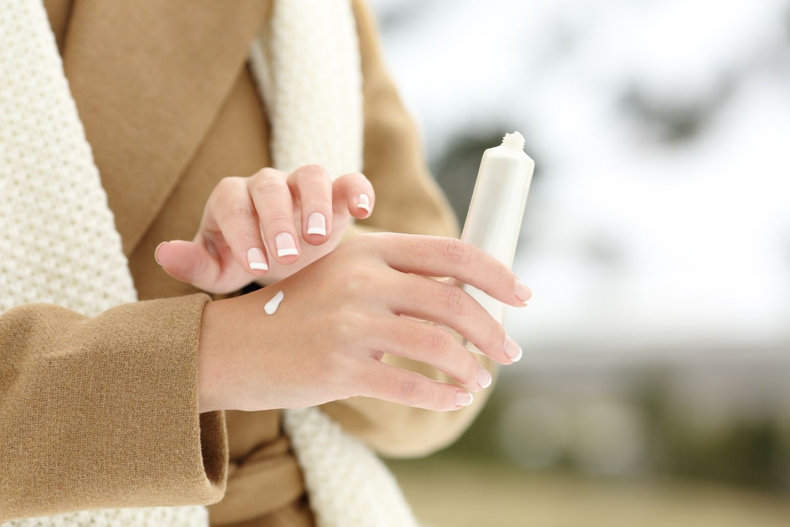 Woman in winter coat rubs lotions onto her dry skin