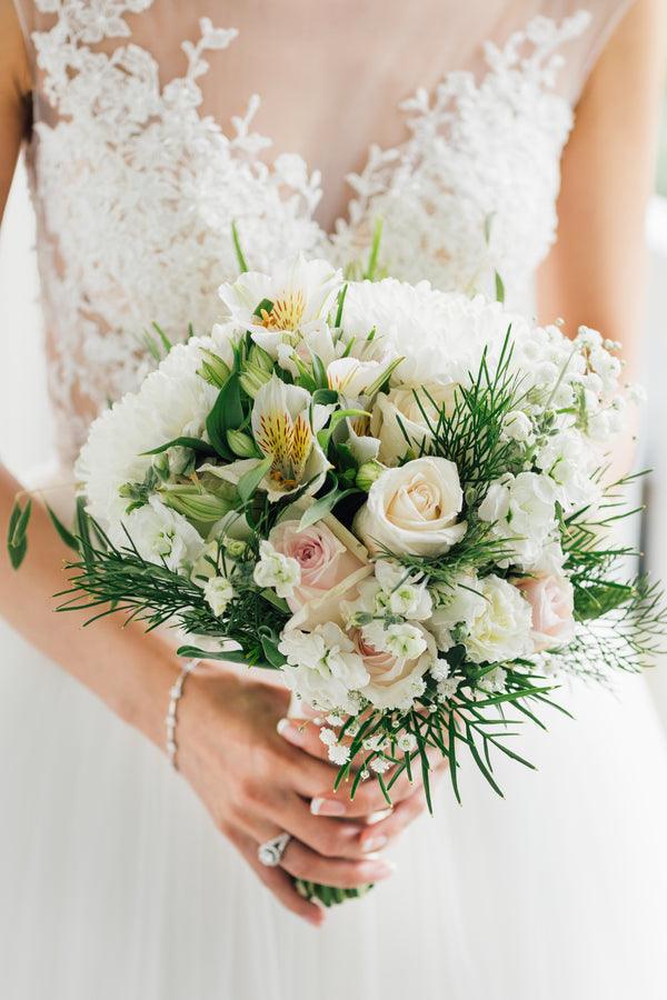 bride in wedding dress made from white lace holding green and white bouquet