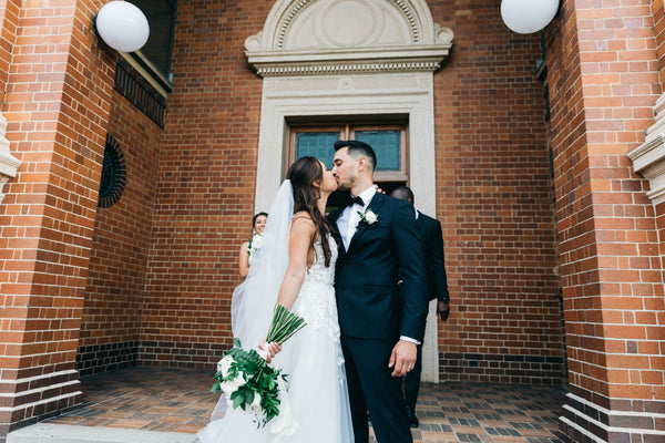 Bride and groom kiss in front of church wedding in Brisbane
