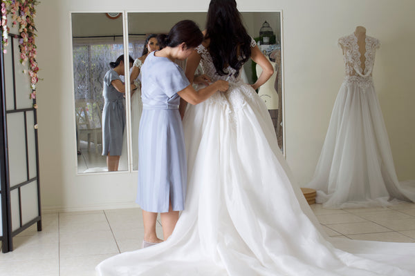 Brisbane wedding dress designer fitting bride into custom wedding gown at bridal studio in front of mirror