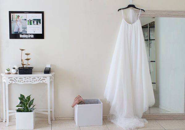 Bridal consult room with a white table featuring an ATM machine, succulent plants, a water feature and a photo hanging above it. To the right of it is a white box and a tall mirror with a white skirt hanging off it