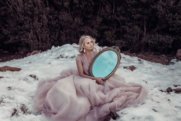 Model in pink lace wedding gown holding a mirror to the sky in the snow