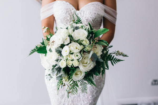 bride wearing wedding dress holding bouquet of flowers