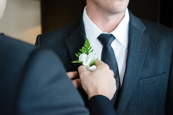 groom preparing for wedding ceremony while father places flowers on grooms suit