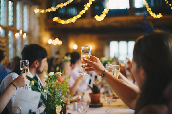guests toasting with glasses of wine at wedding reception