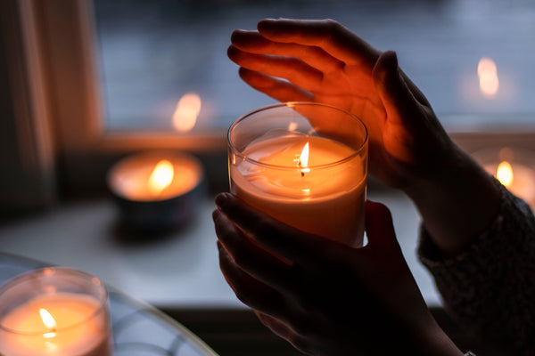 hands holding a unity candle at a wedding ceremony with candles burning in background