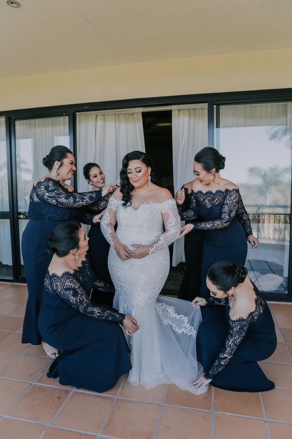 maid of honour and bridesmaids wearing black lace dresses helping bride into her wedding gown