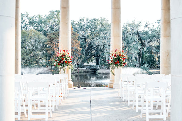 wedding aisle with white seats and bouquets overlooking pond and trees