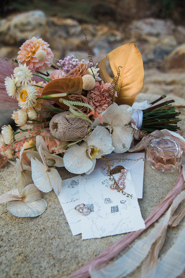 Wedding bouquet with perfume, stationary and wedding rings placed on rock at beach