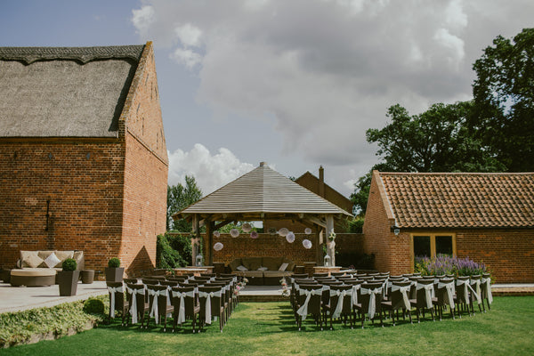 wedding ceremony venue with chairs on grass surrounded by brick buildings