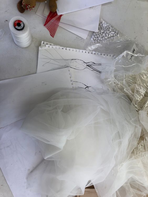 wedding dress sketches on table with fabrics and paper