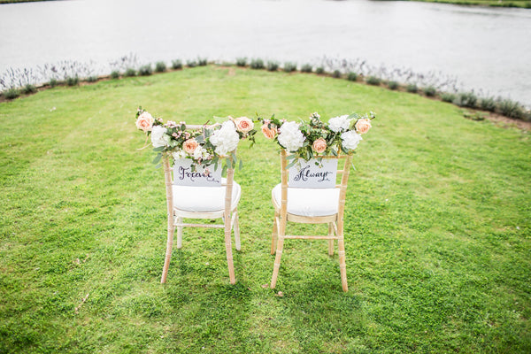 wedding seating for bride and groom covered in flowers on grass