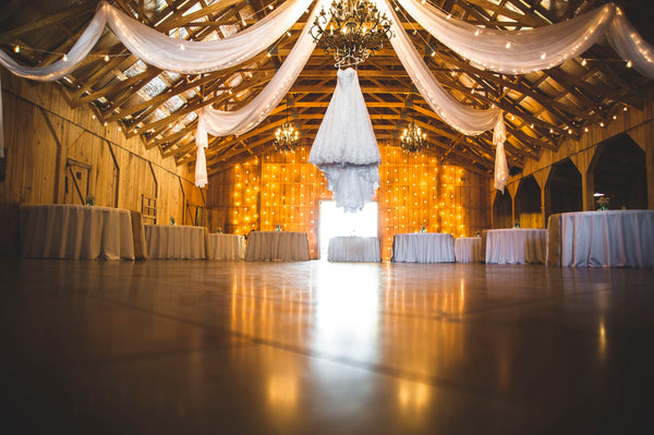 wedding venue with tables and dance floor with tulle hanging from rafters and wedding gown hanging from chandelier