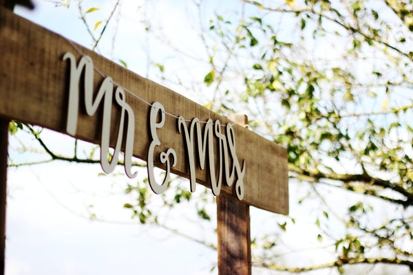 wooden sign with mr and mrs lettering hanging from it