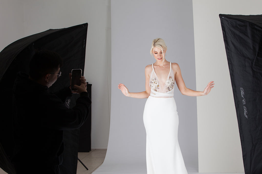 Man in black taking photo of a model in a white dress using an iPhone on a photo shoot set