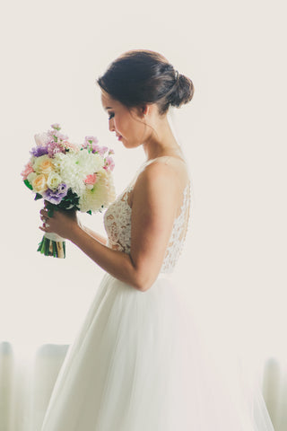 Bride in white lace wedding dress smelling bouquet of flowers