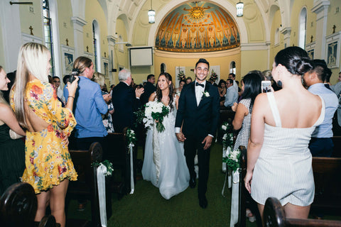 Bride and groom walking down aisle with family around them in Brisbane church